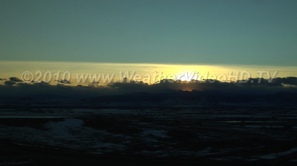 Cold Sunset Winter cap clouds over mountains as sun sets