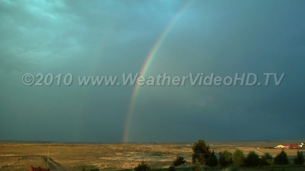 Rainbow Sun shining on storm moving east produces double rainbow