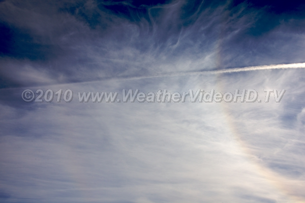Halo and Contrail Icy natural cirrus clouds and a jet contrail exhibit a classic solar halo