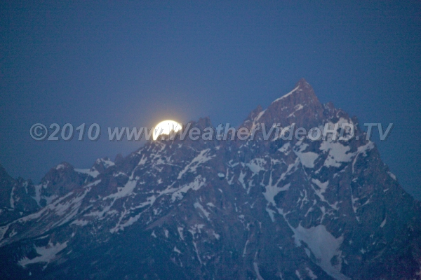 Moonset Behind the Tetons The fill moon about the set behind a snowy peak