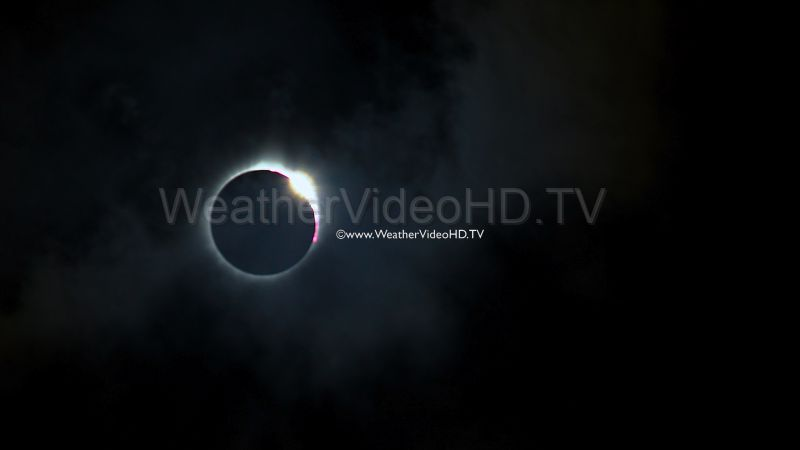 Totality Ends with a Diamond Ring A huge diamond ring appears as the eclipsed sun emerges from behind an obscuring cloud in the seconds when totality is ending. Note the red prominences and corona that show as the clouds depart. Slowed down 50 percent.